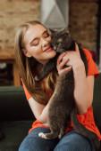 veselá dívka se zavřenýma očima drží v náručí nadýchaná kočka