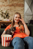 selective focus of sad woman crying near cat and popcorn bucket while watching movie
