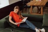 schönes Mädchen liest Buch in der Nähe von Smartphone mit leerem Bildschirm im Wohnzimmer