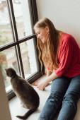 Fotografie mladá a šťastná žena při pohledu na okno v blízkosti roztomilé kočky