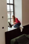 mladá žena sedí na parapetu a dívá se na okno v blízkosti roztomilé kočky