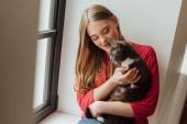 Selektiver Fokus der jungen Frau beim Anblick einer niedlichen Katze in Fensternähe