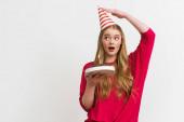 Fotografie překvapená dívka dotýká strana čepice a držení narozeninový dort izolované na bílém