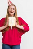 šťastný mladý žena v strana čepice držení dárek izolovaný na bílý