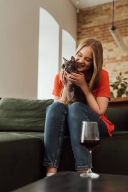 Selective focus of happy young woman holding cute cat near glass of red wine stock vector