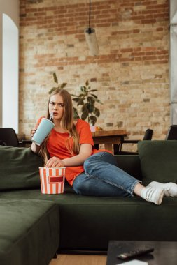 Selective focus of woman drinking soda near popcorn bucket and watching movie in living room stock vector