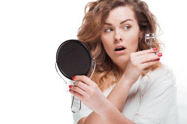 Woman curling eyelashes