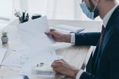 Ausgeschnittene Ansicht eines Geschäftsmannes in medizinischer Maske, der mit Dokumenten am Arbeitsplatz arbeitet