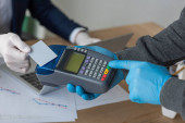 cropped view of businessman holding credit card near delivery man with payment terminal