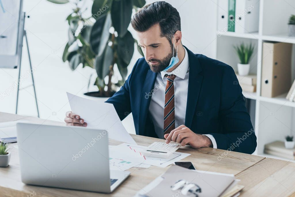 Serious, thoughtful businessman working with documents while sitting at workplace near laptop stock vector