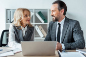 Fotografie Selective focus of smiling businessman looking at businesswoman near papers and laptop on table in office