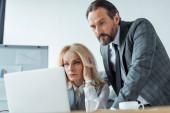 Selektiver Fokus konzentrierter Geschäftsleute auf Laptop im Büro