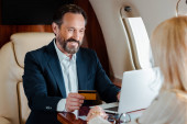 Szelektív fókusz mosolygó üzletember kezében hitelkártya és a laptop közelében üzletasszony repülőn