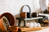 Photo clay mugs and bowls near sharp knife, cotton napkins and raw eggs