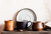 dřevěná lžíce v blízkosti hliněných pohárků a talíř v kuchyni