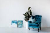 Fotografie bequemer Sessel in der Nähe von Pflanzen und Gemälde im Wohnzimmer