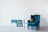 Fotografie bequeme Sessel in der Nähe von Vase auf Couchtisch und Gemälde im Wohnzimmer