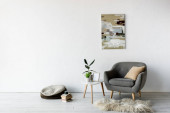 Photo comfortable armchair near coffee table with green plants, frame and painting on wall in modern living room