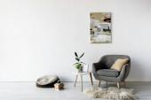 kényelmes fotel közelében dohányzóasztal zöld növényekkel, keret és festmény a falon a modern nappaliban