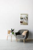 šedé křeslo u konferenčního stolku s rámy a zelenými rostlinami v blízkosti malby na zdi v moderním obývacím pokoji