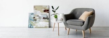 Panoramic crop of comfortable armchair near coffee table with green plants, lamp and paintings in living room stock vector
