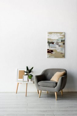 Grey armchair near coffee table with frames and green plants near painting on wall in modern living room stock vector
