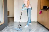 oříznutý pohled na ženu v gumových rukavicích mytí podlahy doma