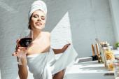 Fröhliche Frau in Handtüchern mit einem Glas Wein in der Küche