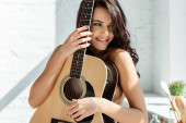 Photo Sensual naked woman smiling while holding acoustic guitar in kitchen