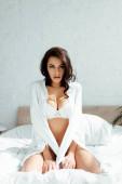 Sexy žena ve spodním prádle a košili sedí na posteli