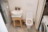 moderní koupelna s WC, umyvadlem a pračkou