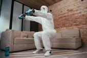 sportovní muž v hazmat obleku, lékařská maska a brýle dělá dřepy cvičení s činkami v obývacím pokoji