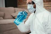 Fényképek férfi vegyvédelmi ruha, orvosi maszk és szemüveg ivóvíz tartása közben sport palack