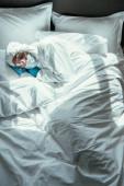felső kilátás férfi vegyvédelmi ruha, orvosi maszk és védőszemüveg alszik az ágyban