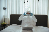 Photo freelancer in hazmat suit, medical mask, latex gloves and goggles touching headphones and using laptop in bedroom