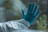 abgeschnittene Ansicht eines Mannes im Latexhandschuh, der Fenster berührt, Quarantäne-Konzept