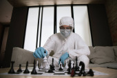 selective focus of man in personal protective equipment and medical mask playing chess