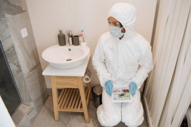 KYIV, UKRAINE - 11 Nisan 2020: Tehlikeli madde giysisi giymiş adam, tıbbi maske, lateks eldiven ve gözlük kullanarak dijital tablet ve ebay uygulaması kullanarak banyo