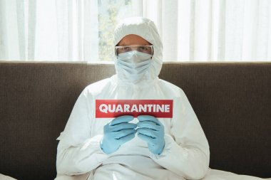 Man in personal protective equipment holding paper with quarantine lettering in bedroom stock vector