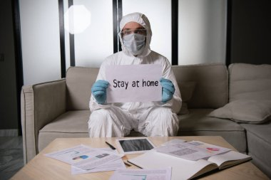 Man in personal protective equipment and latex gloves holding paper with stay at home lettering near digital tablet with blank screen stock vector