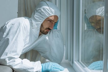 Sad bearded man in personal protective equipment looking at window stock vector