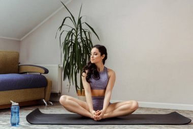 attractive girl in sportswear practicing on yoga mat at home during self isolation