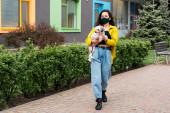 fiatal nő orvosi maszk séta kutya a városban