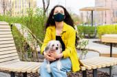 gyönyörű nő fekete orvosi maszk ül padon a parkban kínai crested kutya