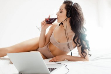 attractive sensual girl in lingerie drinking red wine while having video call with headset and laptop during self isolation
