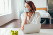Photo thoughtful freelancer in medical mask working on laptop at home with apples on self isolation