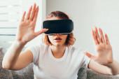 emotivní dívka gestikulace a použití virtuální reality headset doma na karanténě