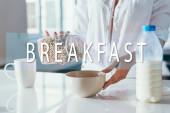 oříznutý pohled dívky s kukuřičnými vločkami s mlékem na karanténě se snídaní nápisy