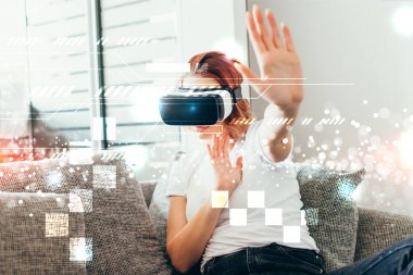 emotional woman gesturing and using virtual reality headset with pixels at home on self isolation