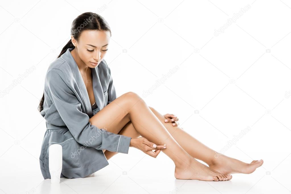 african american woman applying body cream